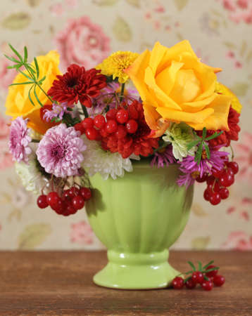 Bouquet of autumn flowers in the green pot  photo