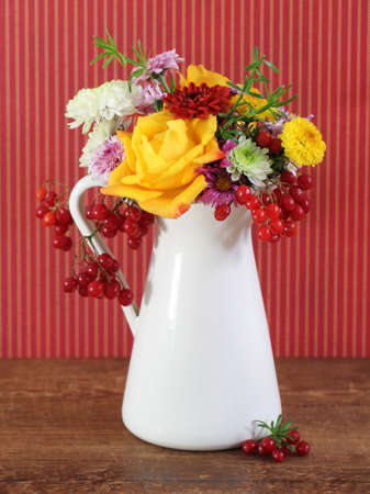Bouquet of autumn flowers in the iron pot over red background photo