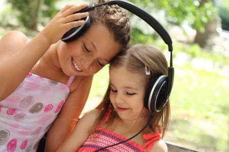 Two sisters listen to the music together outdoor photo