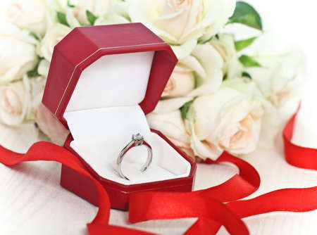 silver ring: Marriage proposal. An engagement diamond ring in the box with roses