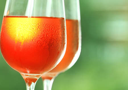 wine colour: Two glasses of a rose wine against green background