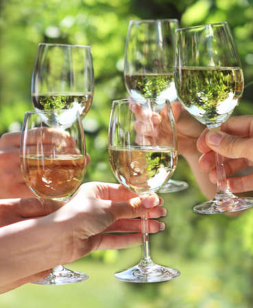 garden party: Celebration. People holding glasses of white wine making a toast