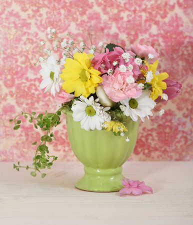 Bouquet of white, yellow and pink flowers in the green vase photo