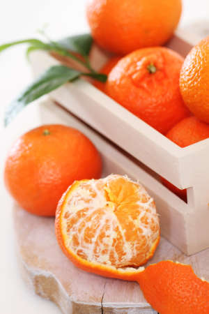 clementine fruit: Fresh citrus fruits in the box on a wooden table Stock Photo