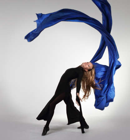 Young blond woman dancing with blue fabric over white photo