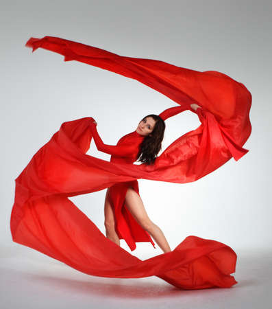 Young brunette woman dancing with red fabric in studio photo