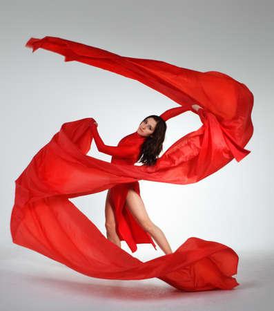 스튜디오에서 빨간색 패브릭 젊은 갈색 머리 여자 춤