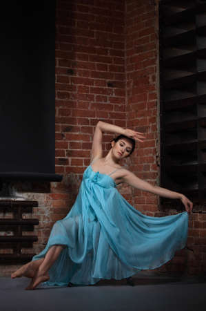 Young brunette woman dancing over brick walls photo