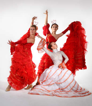Three young women dancing flamenco in studio photo