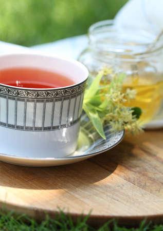 yellow tea pot: Linden honey in a jar with linden flowers and tea in the garden Stock Photo