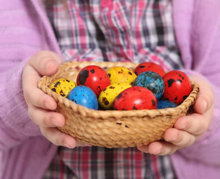 Cute little girl holding basket with easter eggs. Close up photo
