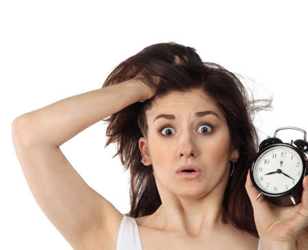 Surprised young brunette woman holding clock in her handin amazement photo