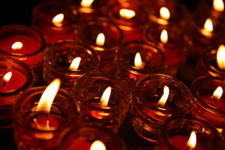memorial candle: Lighting of Praying candles in a temple in dark