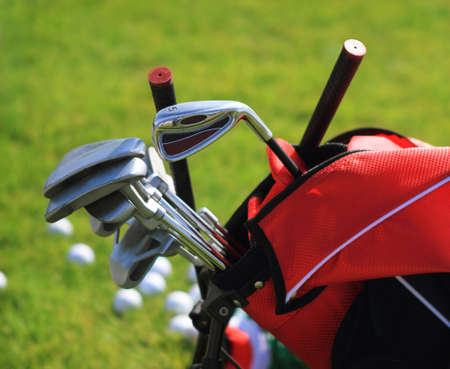 caddie: Golf clubs in golfbag and golf balls green grass background