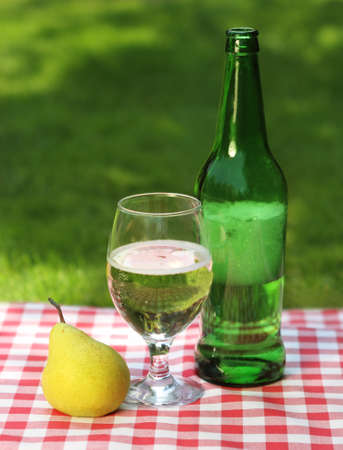 Pear cider and one pear on the summer picnic photo
