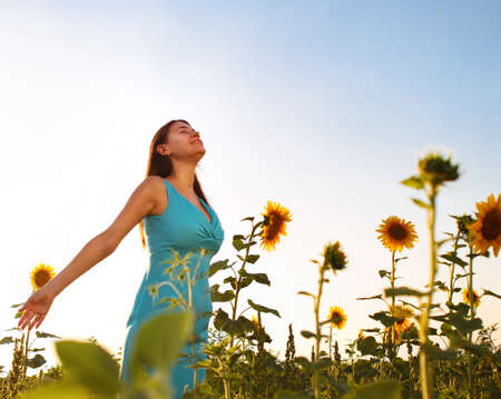 Happy woman in sunflower field in time of sunset photo