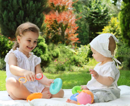 Two playing little sisters in the summer garden photo