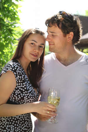 Happy woman and man holding glasses of white wine making a toast photo