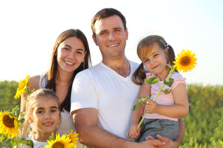 Happy young family with daughters holding sunflowers photo