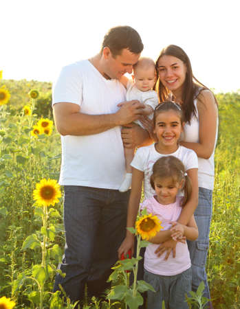 Happy young family with children in sunflowers field photo