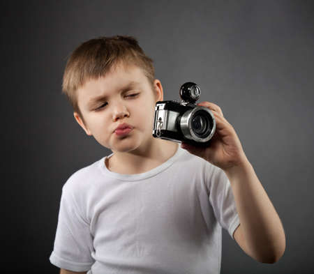 Portrait of the cute little boy with old camera photo