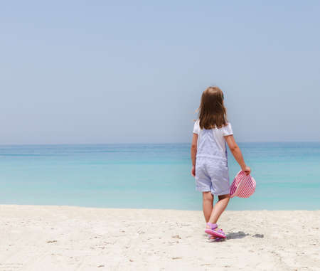 Little girl with hat on the beach photo