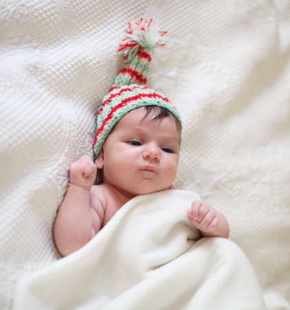 Portrait of a baby in knitting hat lying on the bed. One month old photo