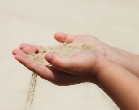 Hands of the child holding dry sand. Drought concept  photo