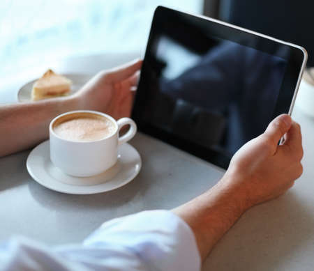 Man holding tablet computer in cafe. Close up photo
