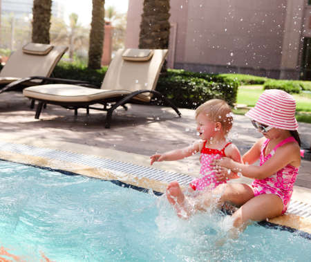 Two little sisters playing in water in swimming pool photo