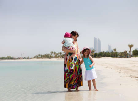 Mother and her two little daughters on the beach photo