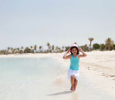 Little joyful girl in hat running on the beach photo