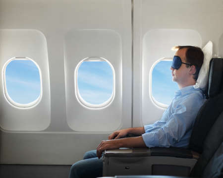 Portrait of man relaxing in sleaping mask in the airplane photo