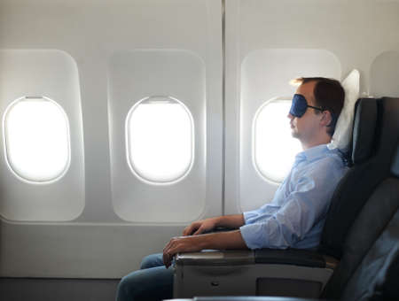 airplane window: Portrait of man relaxing in sleaping mask in the airplane Stock Photo
