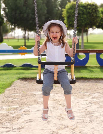 Laughing little girl on swing in summer park photo