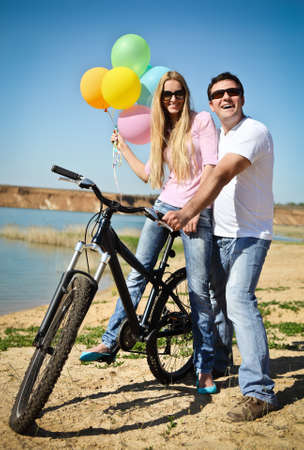 Happy smiling couple with balloons on bicycle photo