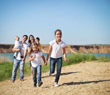 niño corriendo: Familia de joven feliz con los niños al aire libre