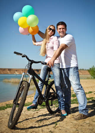 Happy smiling couple with balloons on bicycle Stock Photo - 13639734