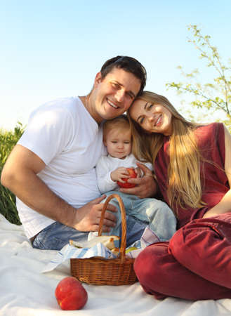Happy young family with child on summer picnic  photo