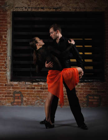 Tango dancers in action against brick wall photo