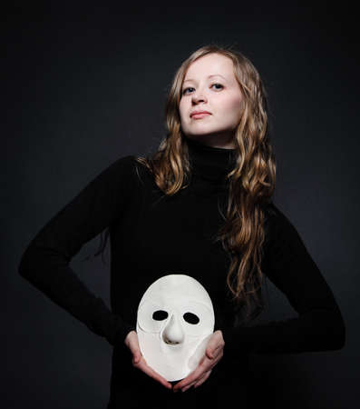 misery: Low key portrait of a beautiful woman with long hair holding mask Stock Photo