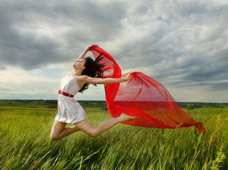Brunette girl jumping with red fabric in summer day. Outdoors potrrait