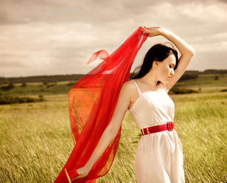 Brunette girl with red fabric in summer day. Outdoors potrrait photo