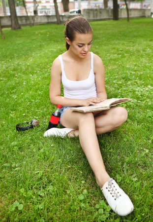 Beautiful young girl with headphones, drink and book on the grass background in summer park photo