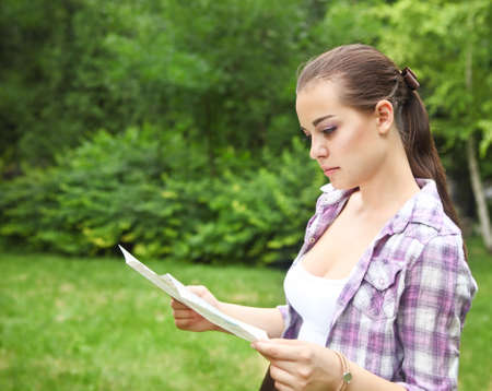 Young brunette girl in the countryside holding a map
