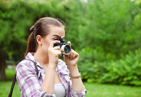 Beautiful smiling young girl with camera outdoors Stock Photo