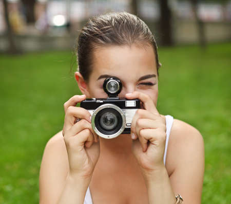 shootting: Beautiful smiling young girl with camera outdoors Stock Photo