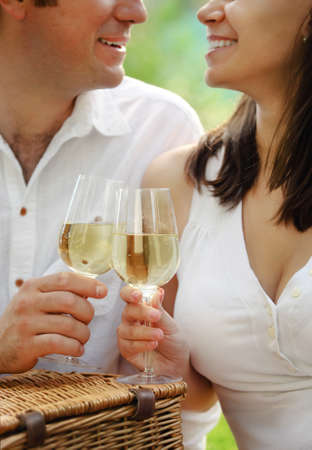 Young happy couple enjoying a glasses of white wine in the garden Stock Photo - 14231651