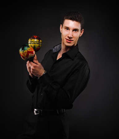 Handsome smiling man with maracas against the black wall photo