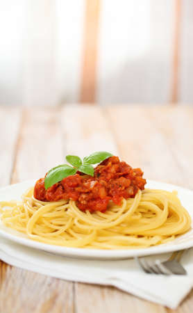 Spaghetti Bolognese on white plate on wooden table photo